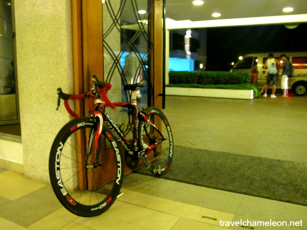 A sporty looking bicycle parked at the main entrance door of the hotel, ready for the competition.