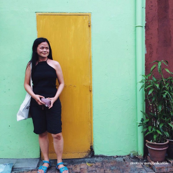 Louise in front of yellow door with lime green wall.