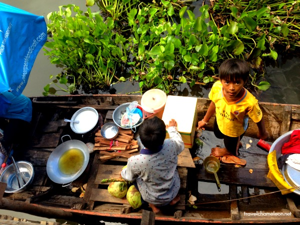 Kids helping their mother cook on a floating boat.