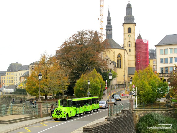 A green train touring the city of Luxembourg with the Church behind it.