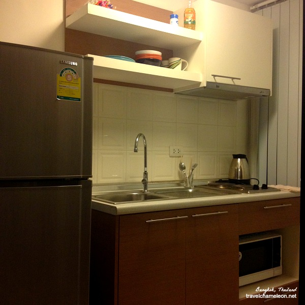 Small kitchen unit with refrigerator, kettle, and a microwave.